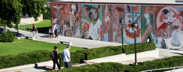 Students walking in front of mural depicting ethnic diversity