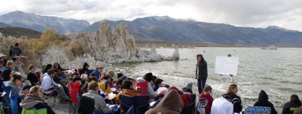 Students sitting next to lake listening to instructor